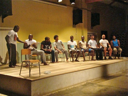 """Ensaios de """"As Orações de Mansata"""" em São Tomé: leitura pública. Da esquerda para a direita: Amador Fernandes (São Tomé e Príncipe), Paulo Figueira (Angola), Rogério Boane (Moçambique), Ridson Reis (Brasil), Wilson Sousa (São Tomé e Príncipe), Trindade Costa (Guiné-Bissau), Igor Lebreaud (Portugal), Miguel Magalhães (Portugal), Jorge Biague (Guiné-Bissau). Foto: Sofia Lobo"""
